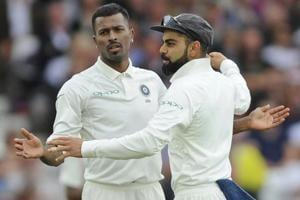 Indian cricket captain Virat Kohli, right, congratulates teammate Hardik Pandya for the dismissal of England