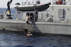 In this photo provided by the Croatian Defence Ministry, a woman who identified herself as Kay from England, climbs aboard a Croatian Coast Guard ship some 90 kilometres from the Croatian coast.