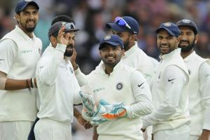 Rishabh Pant, center, stands with captain Virat Kohli, second left, and teammates as they celebrate the dismissal of Adil Rashid.