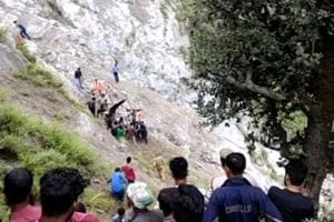 Passersby help in rescue efforts after a vehicle fell down a gorge by the Chenab river in Jammu and Kashmir.