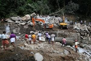 A Public Works Department machine repairs a collapsed bridge after floods at Nelliyampathy Village, in Kerala.