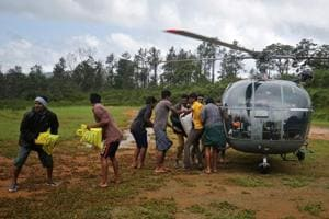 Flood victims unload food and relief material from an Indian Air force helicopter at Nelliyampathy Village, in Kerala, on Tuesday.