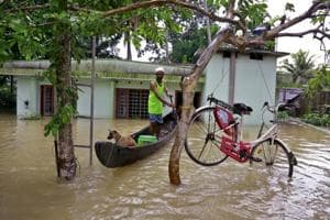 A bicycle is hung from a tree branch to avoid being washed away in flood waters as a man rows with his boat at Kuttanad in Alappuzha, Kerala, on Monday.