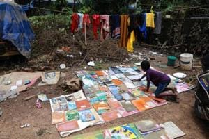 A student dries out his school books after flooding hit his home in Kochi on August 21.