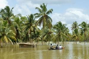 Men take a small boat to travel across flood waters past a marooned farm building to reach their homes in Pandanad in Alappuzha district in Kerala on August 21.