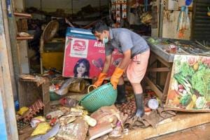 A man salvages the items at his shop after flood water receded at North Paravoor in Kochi on August 20, 2018.