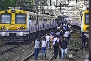 Commuters walking on the track between Sion to Matunga.