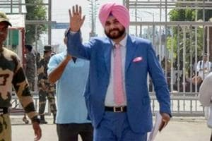 "Punjab minister Navjot Singh Sidhu waves as he crosses the border to attend the swearing-in ceremony of Pakistan prime minister-elect Imran Khan, at Attari-Wagah border in Attari on August 17, 2018. Sidhu, facing criticism for hugging Pakistan's army chief said on Tuesday the gesture was made in an ""emotional moment."""
