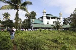 Two Muslim men greet each other after offering Eid prayers at a mosque on the flood affected island of Kunjunnikkara, outskirts of Kochi in the southern state of Kerala, India,.