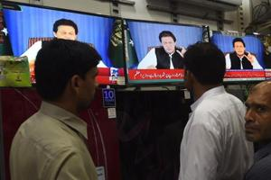 Pakistani men gather around a bank of televisions in a store as they watch a broadcast of a speech of Pakistani Prime Minister Imran Khan, as he addresses the nation, in Lahore on August 19.