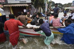 Local fishermen, volunteers and rescue personnel evacuate residents through a boat due to floods at Panadala in Kerala.