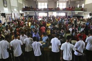 Volunteers serve food to flood affected people at a relief camp set up inside a school in Kochi on August 23, 2018.