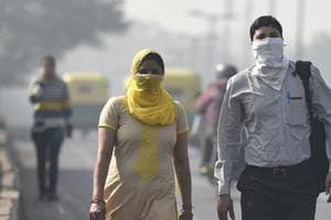Commuters seen wearing face mask to avoid thick smog, as the air quality deteriorated sharply overnight leading to poor visibility conditions across the city, in New Delhi.