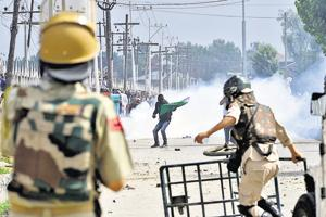 Police paramilitary troopers stand guard as Kashmiri youth protest during clashes in Srinagar.