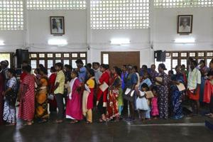 Flood-affected victims stand in a queue for food at a relief camp set up inside a school in Kochi, Kerala.