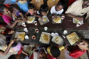 A group of flood affected people, mostly children, sit together to have a meal at a relief camp set up inside a school in Kochi.