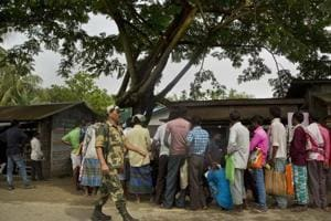 A paramilitary person walks past as people whose names were left out in the National Register of Citizens (NRC) draft stand in a queue to collect forms to file appeals near a NRC center on the outskirts of Guwahati.