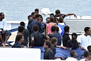 Migrants aboard the Italian Coast Guard ship Diciotti gather as they await decisions in the port of Catania, Italy, on Friday. Italy's populist government warned it would pull European Union funding unless it agrees to take some of the 150 people stranded on an Italian coastguard ship Friday, sparking a fresh immigration row with the bloc.