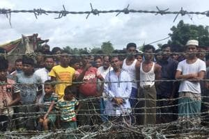 "Rohingya refugees gather near the fence in the ""no man"