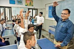 Principal CS Verma (blue shirt) and teacher Suresh Kumar during a happiness class at Kautilya Government Sarvodaya Bal Vidyalaya.