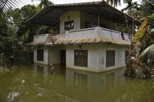 A man wades through water after arriving to inspect his flood affected house in Kuttanad, Alappuzha in Kerala on August 27.
