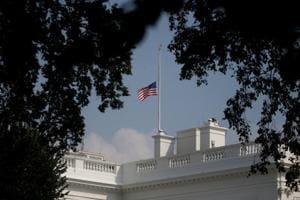 The White House flag flies at half staff in honor of Senator John McCain's death in Washington on Monday.