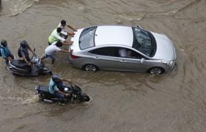 Vehicles get stuck in waterlogged road after heavy rainfall on National Highway 48 near Signature Tower Chowk in Gurugram on Tuesday.