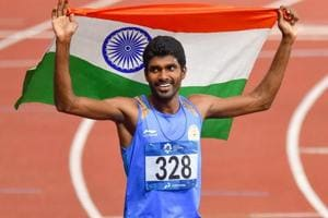 Jinson Johnson celebrate with the national flag after winning gold in Men