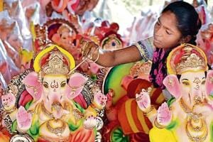 A woman artist painting an idol of Lord Ganesha at a roadside workshop ahead of Ganesh Chaturathi in Amritsar on Tuesday.