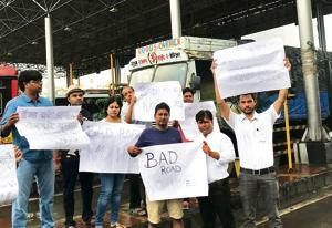 Commuters protest against the battered condition of the Sion-Panvel Highway near Kopra Bridge at Kharghar in Navi Mumbai on Friday.