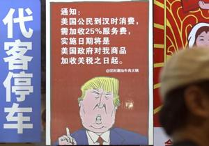 A man walks by a poster depicting a mural of US President Donald Trump speaking on the trade war against China, on display outside a restaurant in Guangzhou in south China