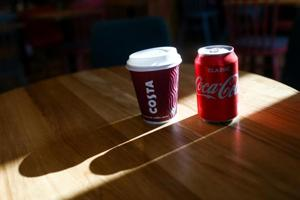 A branded Costa Coffee cup sits next to a can of classic Coca-Cola, manufactured by The Coca-Cola Co., in this arranged photo at a Costa Costa coffee shop in London, U.K., on Friday, Aug. 31, 2018.