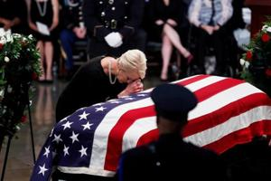 Cindy McCain, wife of late US Senator John McCain, leans over his casket as his body lies in state inside the U.S. Capitol Rotunda in Washington, August 31, 2018.