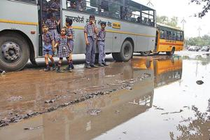 Schoolchildren make their way through a waterlogged stretch, near Kendriya Vidyalaya, on the Old Delhi-Gurugram Road on Friday.