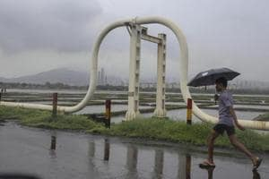 File photo of a pedestrian walking past a pipeline in front of a salt pan in the Mahul area of Mumbai.