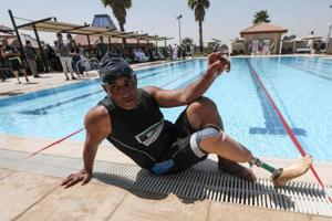 An Iraqi civilian who lost a limb during the government offensive against Islamic State (IS) group jihadists in the northern city of Mosul sits by a swimming pool Arbil, the capital of the Kurdish autonomous region in northern Iraq, on September 1, 2018 during a sportive event sponsored by the Kuwaiti government.