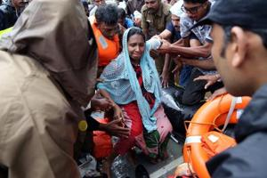 Rescuers help a pregnant woman to disembark a boat after she was evacuated from a flooded area in Aluva, Kerala, August 18, 2018