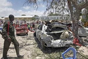 A Somali soldier walks near the wreckage of vehicles at the scene of a blast outside the compound of a district headquarters in the capital Mogadishu, Somalia Sunday.
