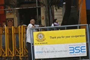 A man looks at a screen across the road displaying the Sensex on the facade of the Bombay Stock Exchange (BSE) building in Mumbai.