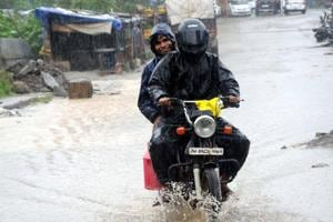 Commuters ride through a water logged Court road in Ranchi, September 2, 2018.