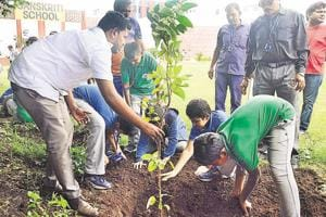 Pavan Randive (left), owner of Guru Krupa nursery, Hadpsar, along with students and faculty members of Sanskriti School, Wagholi, during the HT tree plantation drive at the school campus on September 1.