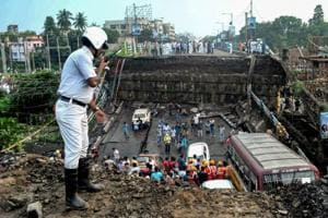 Rescue workers remove debris of the collapsed Majerhat bridge, in Kolkata.