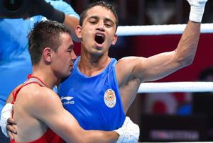 Amit Panghal (in blue) gestures after defeating Uzbekistan