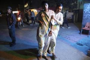 An injured boy is held up outside a hospital following a deadly attack in Kabul on September 5.