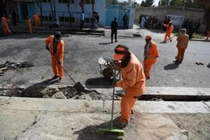 Afghan municipality workers clean the street near the site of a suicide attack, after a blast that targeted wrestlers during a training session at the Maiwand Club, in Kabul on September 6, 2018.