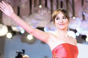 Actress Dakota Johnson waves as she arrives for the premiere of the film Suspiria presented in competition on September 1, 2018 during the 75th Venice Film Festival.