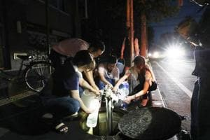 Earthquake-affected residents fill water bottles as an electrical blackout shrouds the shopping district in Sapporo on September 6, 2018, after an earthquake hit the northern Japanese island of Hokkaido.