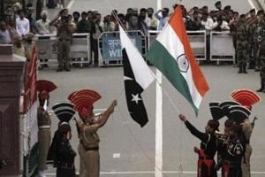 Pakistani rangers (wearing black uniforms) and Indian Border Security Force (BSF) officers lower their national flags during a daily parade at the Pakistan-India joint check-post at Wagah border, near Lahore.