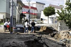 People look at an area damaged by an earthquake in Sapporo in Japan