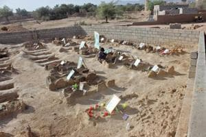 A Yemeni child sits by the graves of schoolboys who were killed while on a bus that was hit by a Saudi-led coalition air strike on the Dahyan market in August, at a cemetery in the Huthi rebels